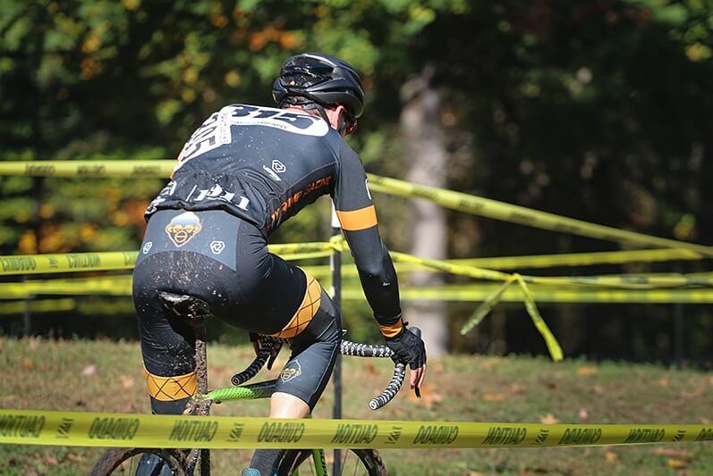 Scott Stewart weaving his cyclocross bike through the tape.